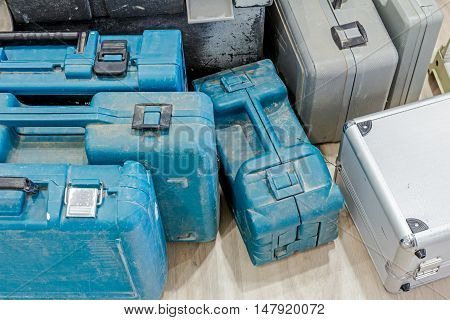 Few various plastic tool boxes are placed on laminate floor in workshop.
