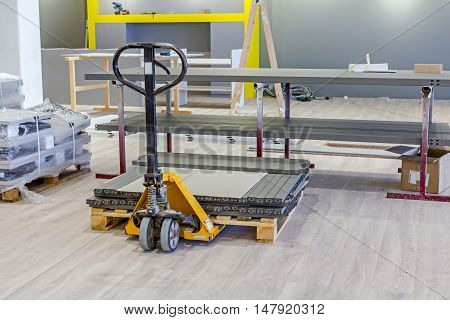 Yellow plastic crates pallet jack pedestrian stacker for transport pallets with furnishing equipment.