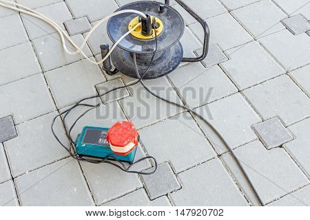 Charging rechargeable battery on power charger for cordless tools connected to extension cord with reel.