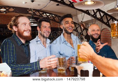 Man Group In Bar Hold Beer Glasses, Standing At Counter Order Barman, Mix Race Cheerful Friends Meeting Pub Communication