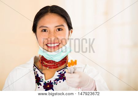 Young beautiful woman dressed in doctors coat and red necklace, facial mask pulled down to chin, holding up syringes smiling happily, egg white clinic background.