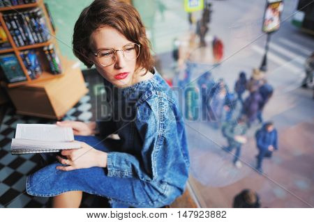 Serious young girl with glasses in a library or bookstore. She sits by the window holding an open book and looking through the window at passing under the windows of people.