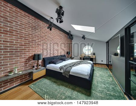 Stylish bedroom in modern style with brick wall and parquet with green carpet on the floor. There is bed, racks with lamps and decorations, round window, table with chair, wall with cupboards and TV.