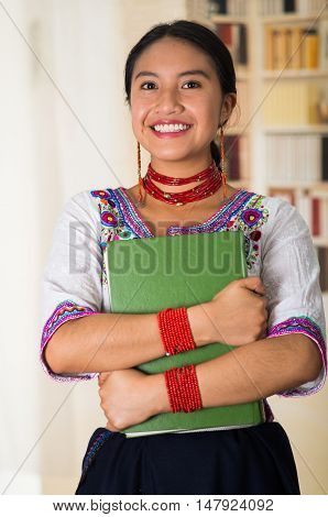 Beautiful young lawyer wearing traditional andean blouse, holding green book smiling to camera, bookshelves background.