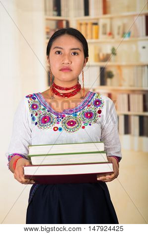 Beautiful young lawyer wearing traditional andean blouse and red necklace, holding stack of books, serious facial expression, bookshelves background.