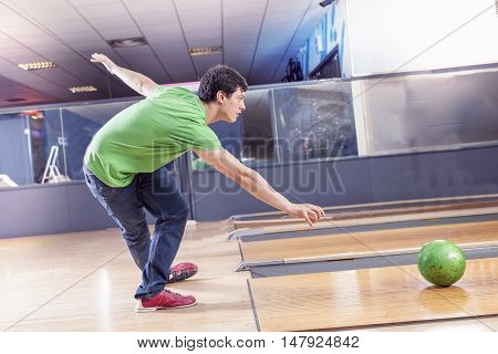 young boy pulls the ball on the bowling alley