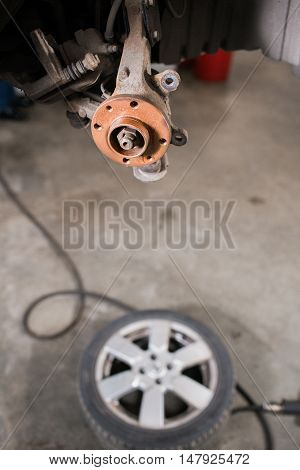 Brand new brake disc on car in a garage. Auto mechanic repairing a car.