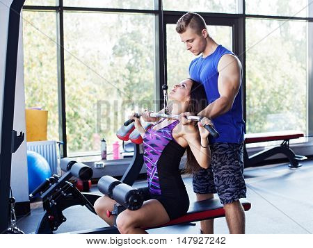 Young athletic woman doing pull down exercise for the back under a personal instructor supervision