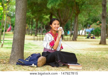 Young woman wearing traditional andean skirt and blouse with matching red necklace, sitting on grass next to tree in park area, relaxing while drinking coffee smiling happily.