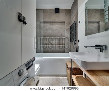 Bathroom in modern style with textured tiles, white sink with tap and mirror, white bath. Opposite the sink there is white locker and washing machine under it. Under the sink there are wooden racks.