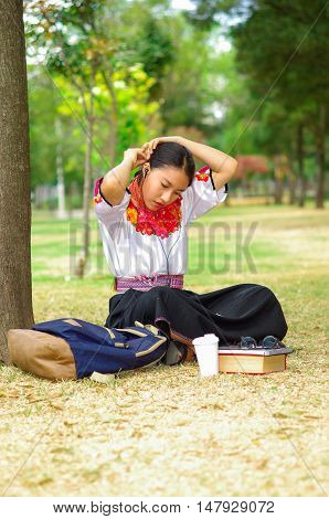 Young woman wearing traditional andean skirt and blouse with matching red necklace, sitting on grass next to tree in park area, relaxing while fixing hair.