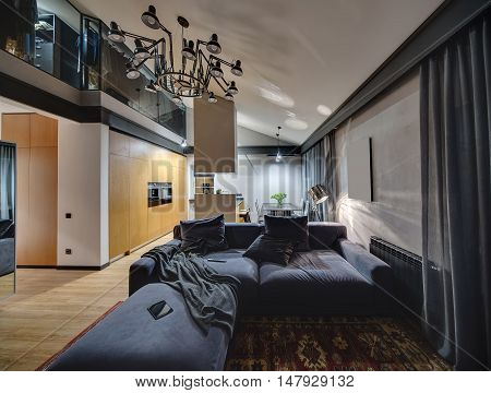 Hall in modern style with glowing lamps and parquet with red carpet on the floor. There is blue sofa with pillows, kitchen island, table with chairs, mirror. Higher there is cloakroom and chandelier.