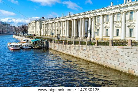 The stone embankment of Fontanka River with the side wall of Baroque Anichkov Palace and the station of the pleasure boats waiting for tourists St Petersburg Russia.