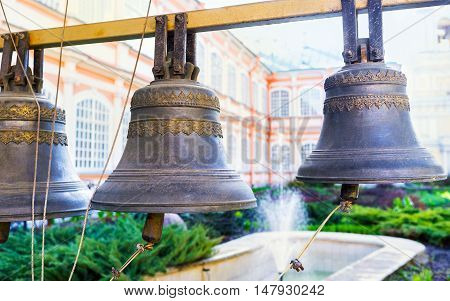 The old monastery bells in Alexander Nevsky Lavra with the fountain on the background Saint Petersburg Russia.