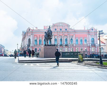 SAINT PETERSBURG RUSSIA - APRIL 25 2015: The statue of the Horse Tamer at the corner of Anichkov Bridge carrying Nevsky Prospekt across Fontanka River and the Museum of Democracy on the background on April 25 in Saint Petersburg.