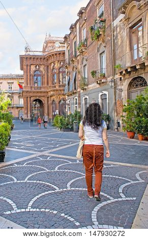 CATANIA ITALY - OCTOBER 10 2012: The street in the old town with the scenic mansions patterns of the paving stone and side view on Massimo Bellini Opera House on October 10 in Catania.