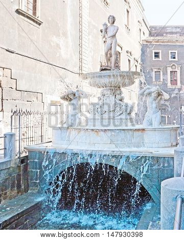 The young boy at the fountain's top symbolize the Amenano River flowing under Duomo Square next to the Chierici Palace in Catania Sicily Italy.