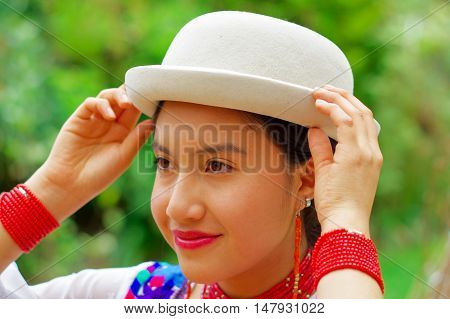 Headshot beautiful hispanic woman wearing, hat, traditional andean white blouse with colorful decoration around neck, matching red necklace, bracelet and ear ring, garden background.