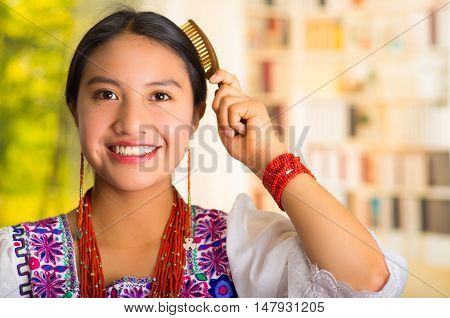 Beautiful hispanic woman wearing white blouse with colorful embroidery, using small hairbrush during makeup routine.