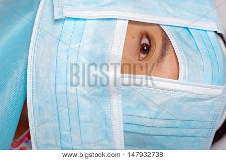 Closeup eye of woman peeking out from total facial cover, preparing for cosmetic surgery concept, doctor using red measure tool.