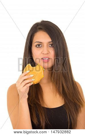 Portrait beautiful young woman posing for camera eating hamburger while making guilty facial expression, white studio background.