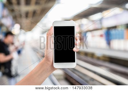 Hand holding mobile phone at railway platform station