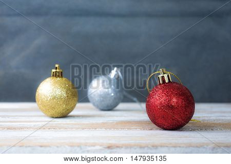 Christmas background with christmas ball, gift, red hat and snow on a wooden background/ Christmas background
