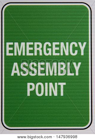 Green and white emergency assembly point signage.
