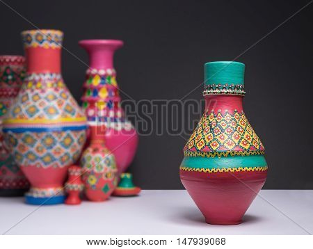 Still life of one decorated painted colorful pottery vase on background of blurred group of colorful vases white table and black wall