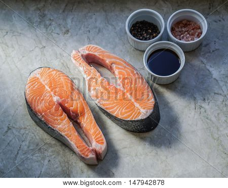Two fresh raw salmon steaks on marble table with soy sauce and spices. Selective focus.
