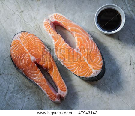 Two fresh raw salmon steaks on marble table. Close-up.
