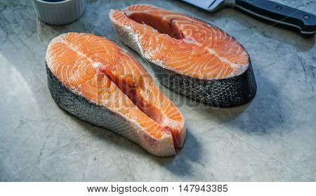 Two fresh raw salmon steaks on marble table. Selective focus.