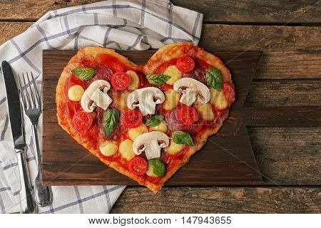 Cutting board with tasty pizza in heart shape and napkin on table