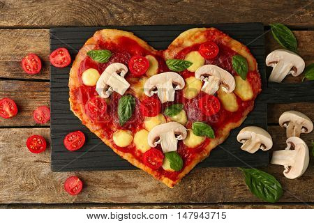 Cutting board with tasty pizza in heart shape on table