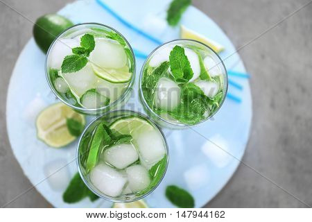 Cold fresh cocktails with lime on wooden board