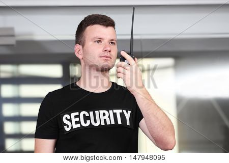 Security man standing beside stairs and using portable radio
