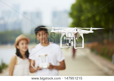 young asian couple operating a drone in a city park selective focus on the drone
