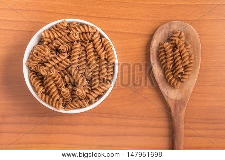 Wholemeal Fusilli into a bowl. Integral Pasta over a wooden table