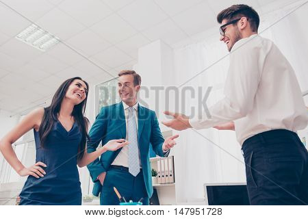 Portrait Of Three Happy Colleagues Discussing New Task And Smiling