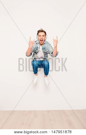 Crazy Young Man Listening Music In Headphones, Jumping And Showing Rock Gesture
