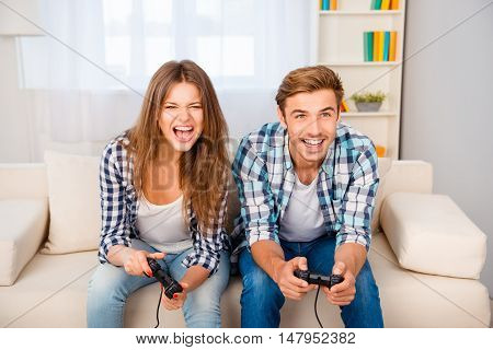 Happy Man And Woman With Joysticks Playing Video Games