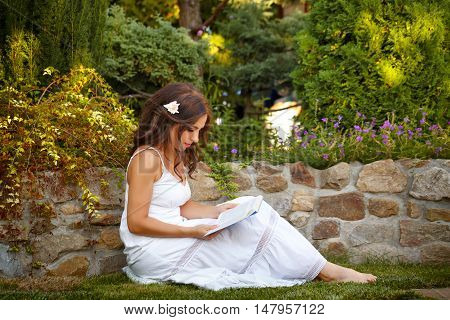 Lovely girl reading a book in the backyard. A girl in a long white dress sitting on the lawn. Reading outdoors air. Self-education.