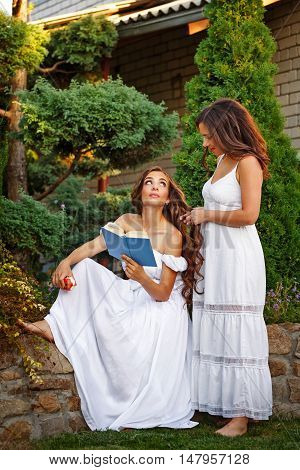 Two sisters. She reads a book and her sister plait her braids. Girls in long white dresses.