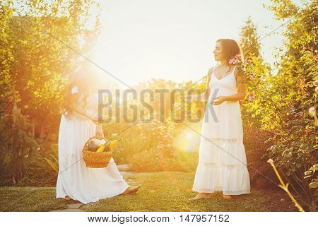 Two cute sisters in long white dresses and a basket with a crop. Girl shows her sister harvest. Ripe fruits and vegetables. Rich harvest. Agriculture.