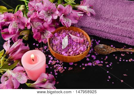 Spa and wellness setting with salt, candles and towel, petals