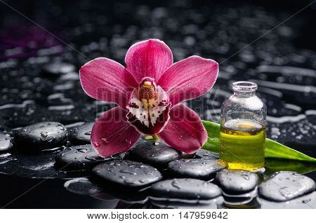 Red orchid ,with oil ,leaf and therapy stones