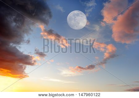Clouds moon is a vibrant colorful cloudscape at sunset with an ethereal full moon rising in the sky.