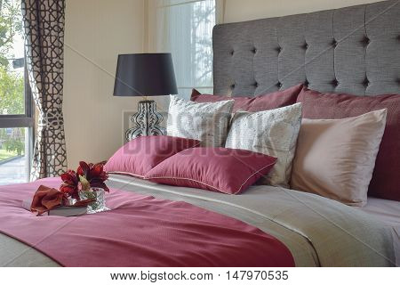 Colorful Pillow and decorative tray with book flower on the bed
