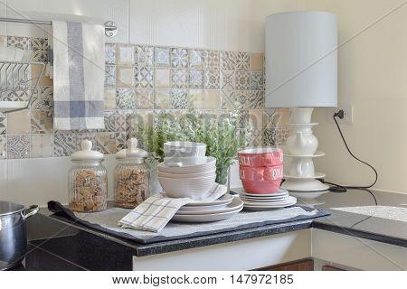 modern ceramic kitchenware and utensils on the black granite countertop