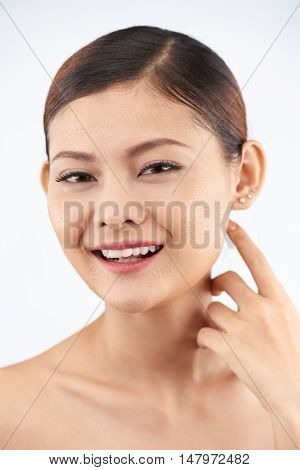 Attractive Asian woman with pure skin smiilng at camera